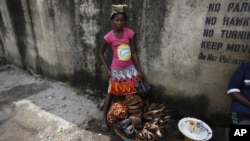 Twelve-year-old, Kemi Olajuwon, who has to drop out of school some days to sell smoked fish and make money so there can be food in the house, and also for her school fees, displays her fish on the street in the Obalende area of Lagos, Nigeria, Tuesday, June 17, 2014.