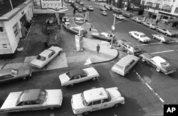 FILE - Cars line up in two directions at a gas station during fuel shortages brought about by an Arab oil embargo, in New York City, Dec. 23, 1973. The embargo was among the factors that pushed the U.S. government to pursue greater vehicle fuel efficiency.