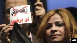 """Une journaliste brandit une carde sur laquelle est écrit : """"Nous n'avons pas peur du terrorisme du groupe Etat islamique"""" lors d'une manifestation au Caire, Egypte, 18 février 2015."""