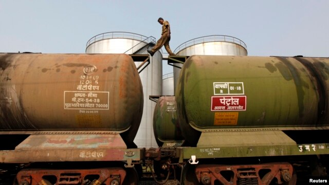 FILE - A worker walks atop a tanker wagon to check the freight level at an oil terminal on the outskirts of Kolkata, Nov. 27, 2013.
