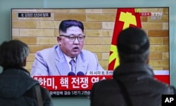 FILE - South Koreans watch a TV news program showing North Korean leader Kim Jong Un's New Year's address, at the Seoul Railway Station in Seoul, South Korea, Jan. 1, 2018.