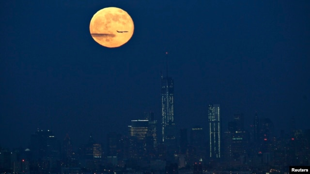 A full moon is seen in the sky behind New York's Lower Manhattan skyline in this June 23, 2013, file photo.