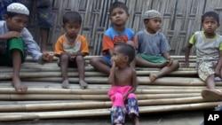 Anak-anak Rohingya yang tampak kekurangan gizi duduk di atas tumpukan bambu di kamp Dar Paing, utara Sittwe, negara bagian Rakhine, Myanmar (foto: ilustrasi).