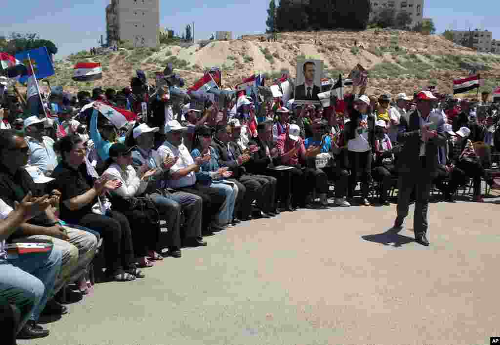 In this photo released by the Syrian official news agency SANA, backers of President Bashar al-Assad hold his portrait and wave Syrian flags during a demonstration in support of his candidacy for another term as president, Damascus, Syria, May 23, 2014.