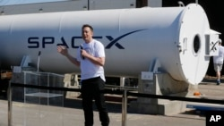 FILE - Telsa CEO Elon Musk congratulates the winners of the Hyperloop Pod Competition II at SpaceX's Hyperloop track in Hawthorne, Calif., Sunday, Aug. 27, 2017.