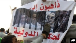 An anti-Mubarak protester uses a shoe to beat an image of former president Hosni Mubarak along with his sons and former Interior Minister Habib al-Adli in front of the police academy where Mubarak is on trial in Cairo, Egypt, September 5, 2011.