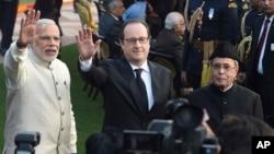 인도를 방문 중인 프랑수아 올랑드 프랑스 대통령(가운데)이 나렌드라 모디 인도 총리(왼쪽)와 함께26일 뉴델리에서 열린 인도 공화국 창건일 기념행사에 참석해 기자단을 향해 손을 흔들고 있다.