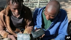 FILE - Two men listen to a battery-operated radio for results of the country's 2008 elections, in Bulawayo, Zimbabwe.