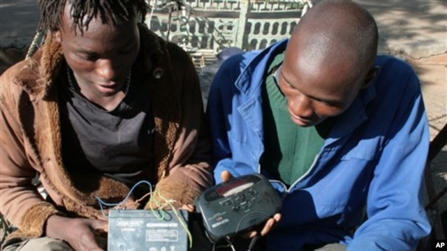 FILE - Two men in Bulawayo, Zimbabwe listen to a battery-operated radio for the results of the country's 2008 elections.