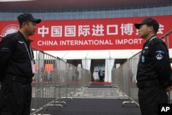 Security guards stand on duty near an entrance to the China International Import Expo in Shanghai, November 5, 2018.