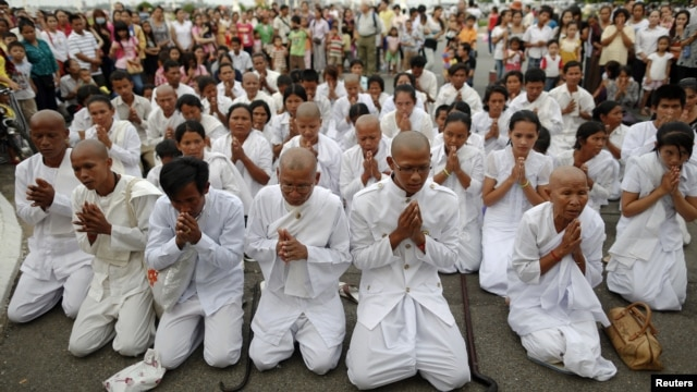 People wearing white pray as they mourn Cambodia's former King Norodom Sihanouk in front of the Royal Palace in Phnom Penh, October 15, 2012.