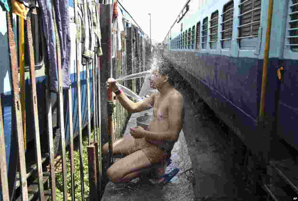 An Indian passenger takes a bath at a railway station during a severe heat wave where temperatures have reached 48 degrees Celsius, in Jammu, May 25, 2015.