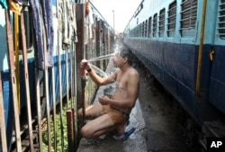FILE - An Indian passenger takes a bath beside rail tracks on a hot summer day at a railway station in Jammu, India, May 25, 2015.
