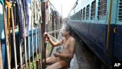 An Indian passenger takes a bath beside rail tracks on a hot summer day at a railway station in Jammu, India, Monday, May 25, 2015. Severe heat wave conditions continue to prevail at several places in northern India with temperatures reaching 48 degrees C
