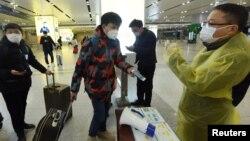中国浙江省杭州市火车站一名旅客使用手机中的绿色健康码向车站检疫人员显示他的健康状况。(2020年2月17日)