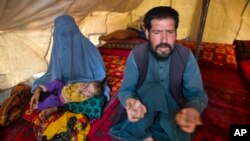 FILE - Mohammad Azam, whose pregnant teenage daughter Zarah died after being set on fire in her husband's home, speaks about her death while an unidentified woman and child rest nearby in Kabul, Afghanistan, July 18, 2016. Azam traveled to the capital to call for justice.