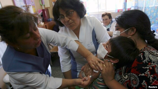 FILE - A nurse vaccinates a child against hepatitis to prevent disease in Constitucion, Chile.