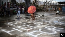 "Survivors of Typhoon Haiyan walk over a ""Help"" message painted on a concrete floor, Saturday, Nov. 16, 2013 in Burauen town, Leyte province, central Philippines."