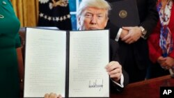 President Donald Trump holds up an executive order in the Oval Office of the White House, Feb. 3, 2017. The executive order will direct the Treasury secretary to review the 2010 Dodd-Frank financial oversight law.