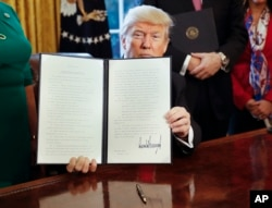 FILE - President Donald Trump holds up an executive order in the Oval Office of the White House, Feb. 3, 2017. The executive order directed the Treasury secretary to review the 2010 Dodd-Frank financial oversight law.