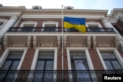 FILE - The Ukrainian national flag flies at half-staff at the Ukrainian Embassy in The Hague after the loss of a Malaysia Airlines plane over rebel-held territory in eastern Ukraine, July 18, 2014.