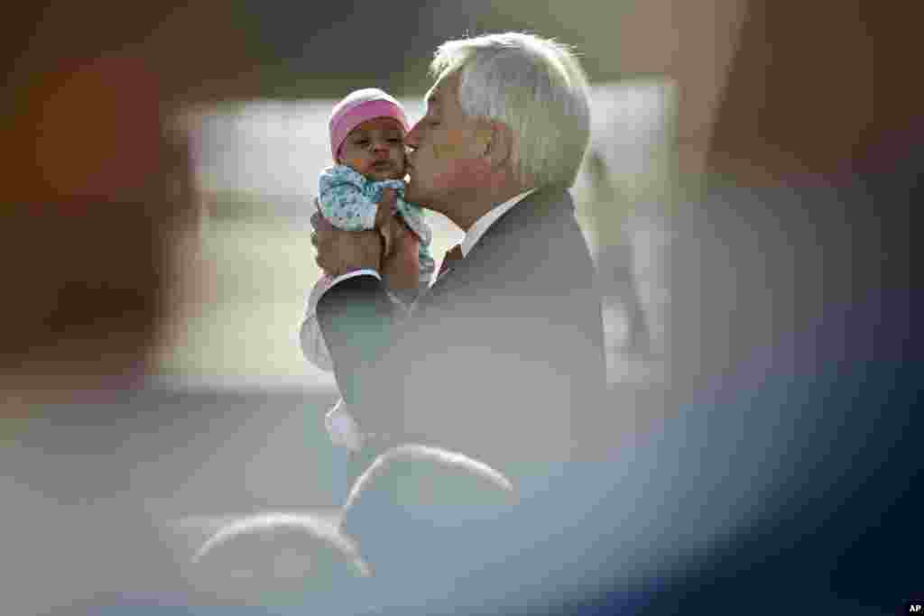 Chile's President Sebastian Pinera kisses a baby as he receives a group of repatriates at the international airport, in Santiago.