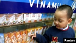 FILE - A Vietnamese boy looks at dairy products at a showroom of the Vietnam Dairy Products Co (Vinamilk) in Hanoi.
