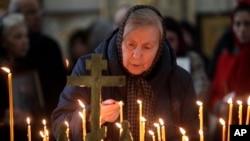 Une femme allume une bougie lors d'un service religieux dans la cathédrale de Saint-Pétersbourg en hommage aux victimes de l'attentat dans le métro de la ville, Russie, le mercredi 5 avril 2017.