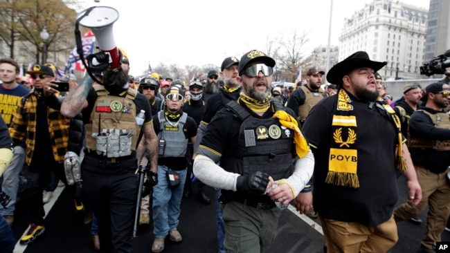 Supporters of President Donald Trump who are wearing attire associated with the Proud Boys attend a rally at Freedom Plaza, Saturday, Dec. 12, 2020, in Washington. (AP Photo/Luis M. Alvarez)