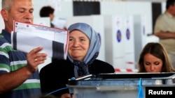 Cử tri bỏ phiếu tại một phòng phiếu trong thủ đô Pristina của Kosovo, 8/6/14