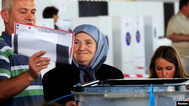 A Kosovo Albanian woman places her ballot paper into a voting box at the polling station in the capital city Pristina, June 8, 2014.