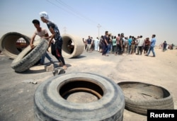 Iraqi protesters move tires and concrete blocks to block the road during a protest in south of Basra, Iraq July 16, 2018.