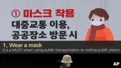 在南韓首爾東大門設計廣場,一名戴著口罩的婦女經過顯示預防冠狀病毒的屏幕。(2020年4月19日)