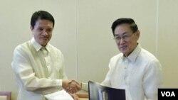 Ketua delegasi Filipina Alexander A. Padilladan berjabat tangan dengan Ketua Partai Demokratik Komunis Luis G. Jalandoni. (2/15).