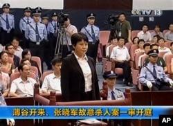 中央电视台画面显示薄熙来妻子谷开来(中间站立者)2012年8月9日在中国东部的合肥市中级人民法院出庭受审