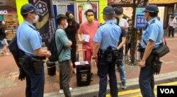 多名军装及便衣警员,截查摆街站反对当局收紧查册安排的工会成员 (美国之音/汤惠芸)