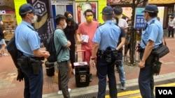 多名軍裝及便衣警員,截查擺街站反對當局收緊查冊安排的工會成員 (美國之音湯惠芸)