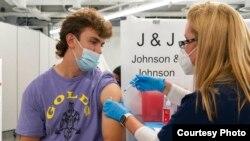 Bradley Sharp asal Saratoga New York menerima vaksin COVID-19 Johnson & Johnson dari perawat, Stephanie Wagner di New York. Bradley perlu divaksinasi COVID-19 karena diwajibkan oleh kampusnya (dok: AP Photo/Mark Lennihan)