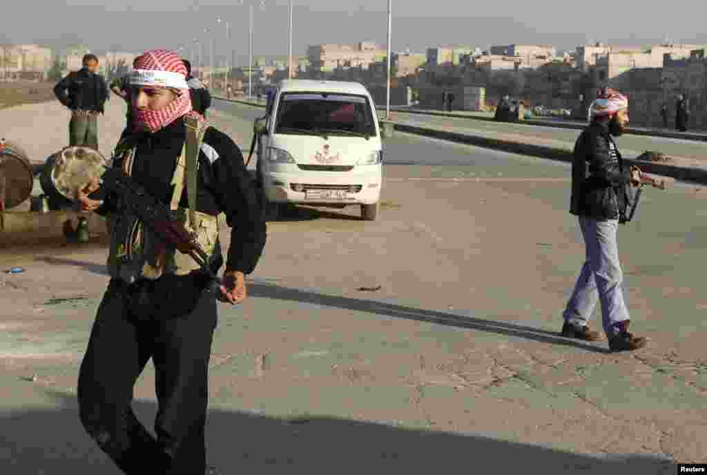 Free Syrian Army fighters man a checkpoint to prevent members of the al Qaida-affiliated Islamic State of Iraq and the Levant from entering Masaken Hanano in Aleppo, Jan. 7, 2014.