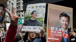 Supporters of Hong Kong pro-Beijing by-election candidate Vincent Cheng Wing-shun and pro-democracy by-election candidate Edward Yiu, show their promotional posters during an election campaign in Hong Kong, March 11, 2018.