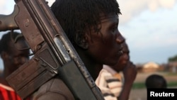 A man from the Lou Nuer tribe carries his gun in Yuai Uror county, South Sudan, July 24, 2013.
