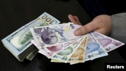 A money changer holds Turkish lira banknotes next to U.S. dollar bills at a currency exchange office in central Istanbul, April 15, 2015.