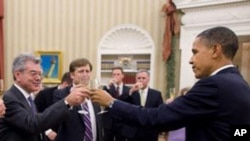 President Barack Obama shares a toast in the Oval Office with the members of his National Security Staff who worked on the New START nuclear arms control agreement, 22 Dec 2010