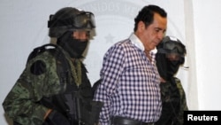 FILE - Soldiers escort head of the Beltran Leyva drug cartel Hector Beltran Leyva in Mexico City, in this handout picture taken Oct. 1, 2014 by the Attorney General's Office.