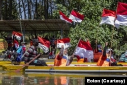 Aktivis Perempuan Pejuang Kali Surabaya melakukan upacara bendera di atas sungai sekaligus mengawali ekspedisi susur sungai. (Foto: Courtesy/Ecoton)