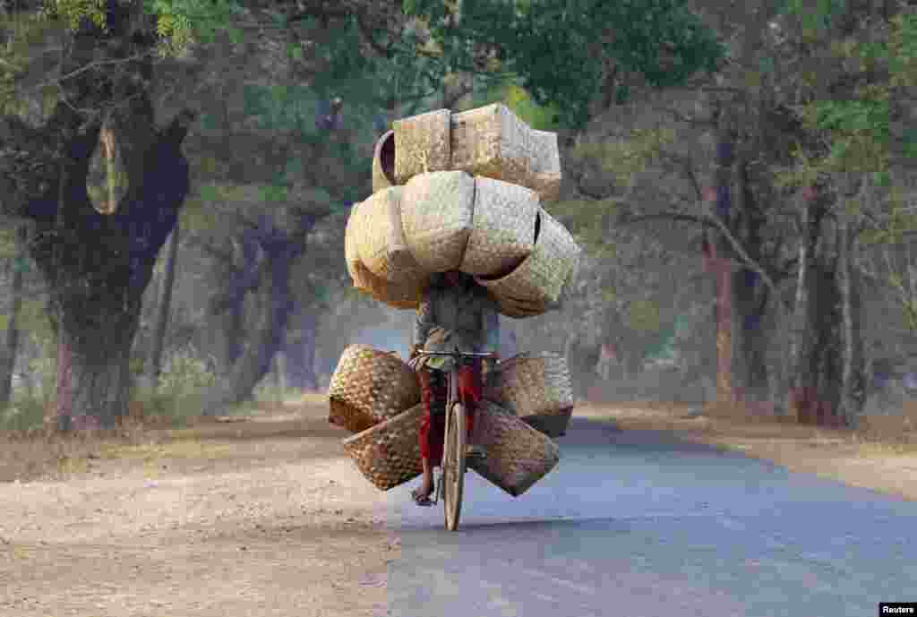 A woman cycles as she carries baskets to sell in a market near Lapdaung mountain in Sarlingyi township, Burma.