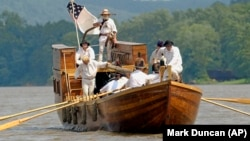 Re-enactors of the Corps of Discovery retrace the steps of Lewis and Clark. (AP Photo/Mark Duncan)