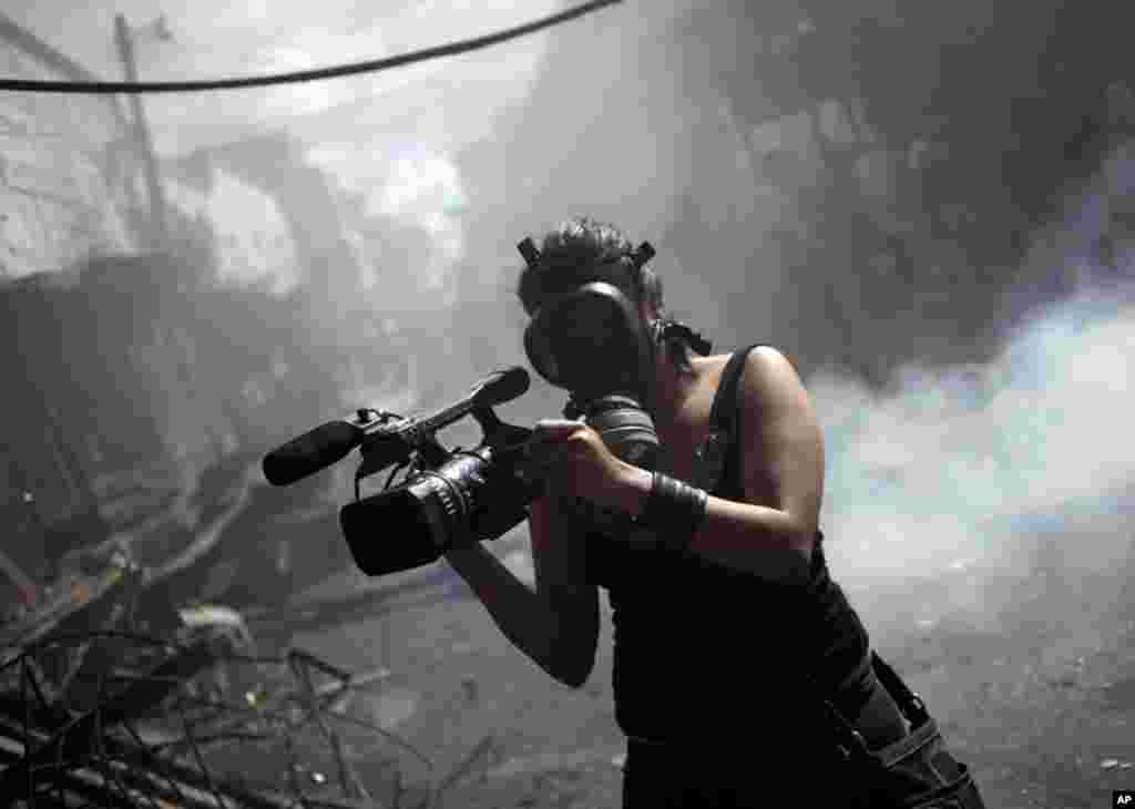 A member of the local media records a fire at the Comayaguela market in Tegucigalpa, Honduras, February 18, 2012. (Reuters)