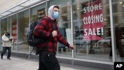 Stanovnik Bostona prolazi pored radnje koja najavljuje zatvaranje u izlogu (Foto: AP/Steven Senne)