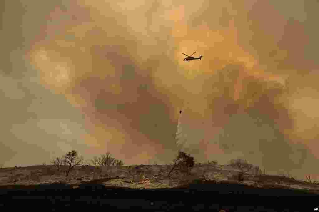 یک هیلیکوپتر امداد آب روی آتش در منطقه سنتا آنا می ریزد. چند هزار آتشنشان در حال مهار آتشسوزی کالیفرنیا هستند.